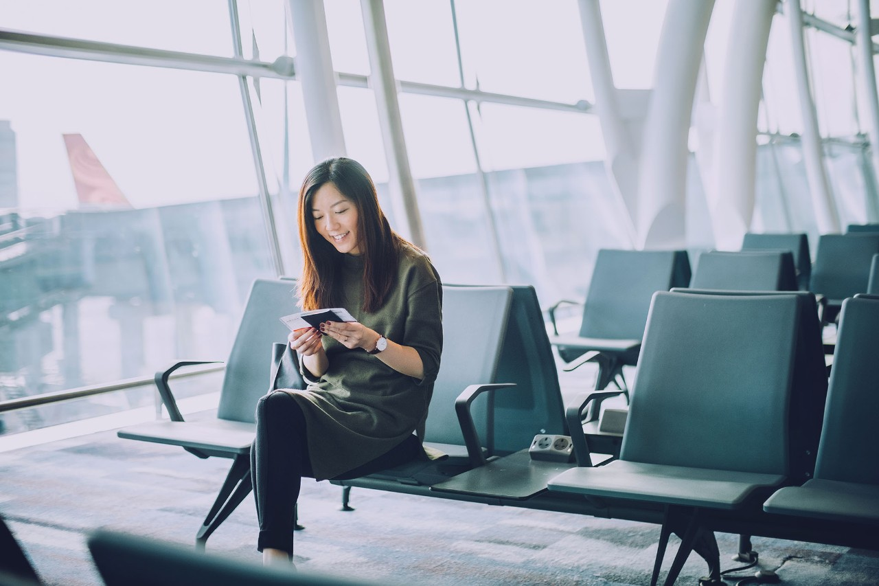 Young woman holding passport and boarding pass waiting in the departure lounge in airport, individual, plane, phone, mobile, device, travel, Asian