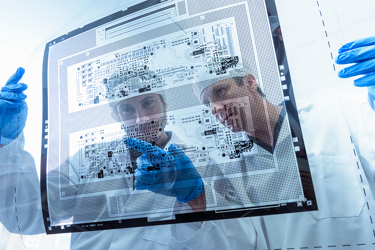 Workers inspecting circuit board negative sheet in factory, science, two people