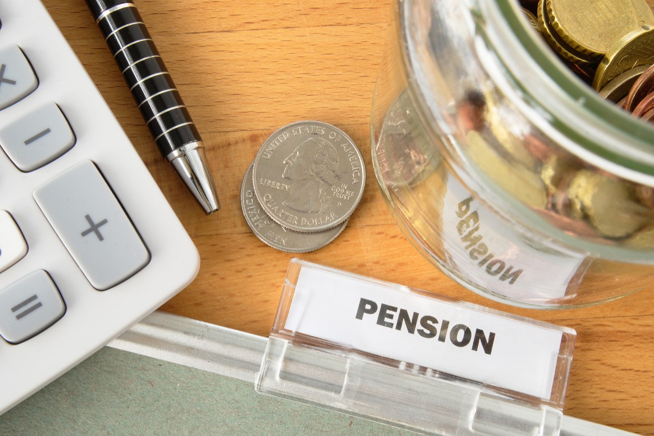 Pension file with calculator, pen, coins and glass jar
