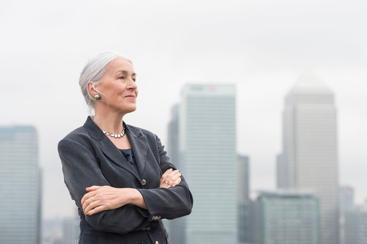 Confident mature businesswoman with arms crossed on city office roof terrace, London, UK, individual, buildings, woman, leader