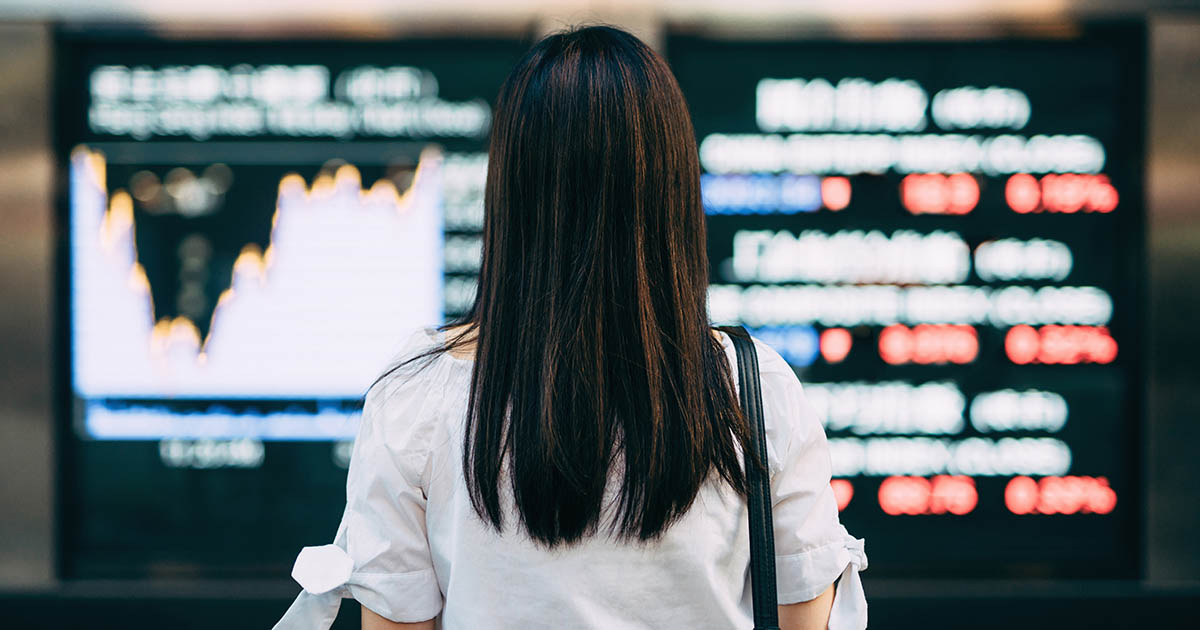 1167016699 Rear view of businesswoman looking at stock exchange market display screen board in downtown financial district